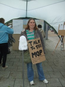 a photo of Sarah carrying her a mop with a board saying talk to the mop.  image copyright
