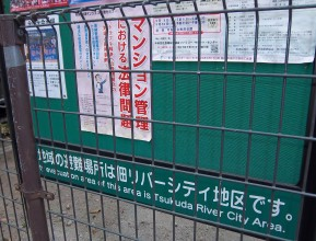 Photographed through some railings this green, street notice board, besides some current information posters, also explains where the nearest safe evacuation point is: Tsukuda River City Area.