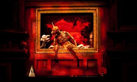 puppets portraying the devil and mr punch are pictured in dialogue, sitting inside a red window frame, against a red background
