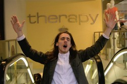 photo of young man with long hair raising his arms at the top of an escalator. He is wearing a strait jacket beneath a suit and on the wall behind him is a sign saying 'therapy'
