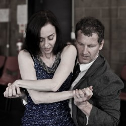 photo of Michelle Ryan standing with her arms crossed and an expression of concentration on her face as Vincent Crowley holds her, supporting her right arm with his left hand