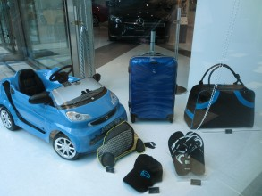Shop window in a car showroom, this photo shows a child`s blue pedal car and various blue and black branded accessories on a white background. The bonnet of a black Mercedes Benz is visible in the background