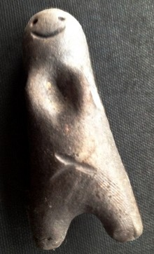 a very simple handmade impression of a person, a body with stumpy legs; a smile and an x marking the belly-button; this is black Zambian clay baked in the African sun.