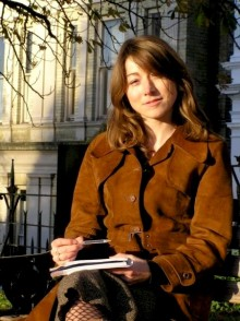 photo of poet nicole hodges wearing a brown coat, sitting outside an old building