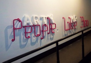 The Pink Grab rails on the white wall with large white felt letters spelling ARTY propped up on the 'People' section
