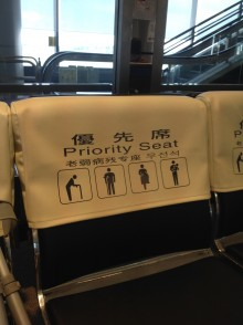 Photo of the slip cover on the back of a priority seat at Narita airport. The white cover is printed in black, with images of an elderly person, person on crutches, a pregnant woman and a person with a small child.