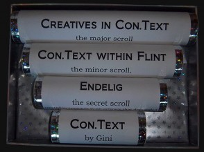 Four white tubes in decreasing lengths, displayed in a box lined with silver stars. Each tube has a title: 'Creatives in Con,Text, the major scroll; Con.Text within FLINT, the minor scroll; Endelig, the secret scroll and the shortest tube Con.Text by Gini