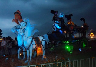 This dark blue image, with the moon visible in the background, shows two life-size plastic cartoon horses pulling an old fashioned spooky-looking coach driven by a disney ghost.The coach wheels have green lights, the horses orange ang black livery, but th