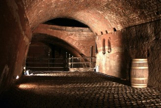 photo of the inside of an arched Victorian brick tunnel with cobblestone floor