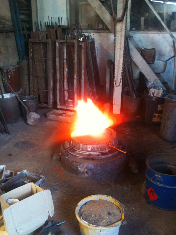 shows a crucible full of molten metal in the middle of a foundry