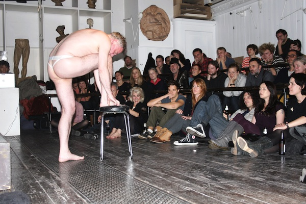 photo of artist Aaron WIlliamson, performing semi-naked in front of an audience
