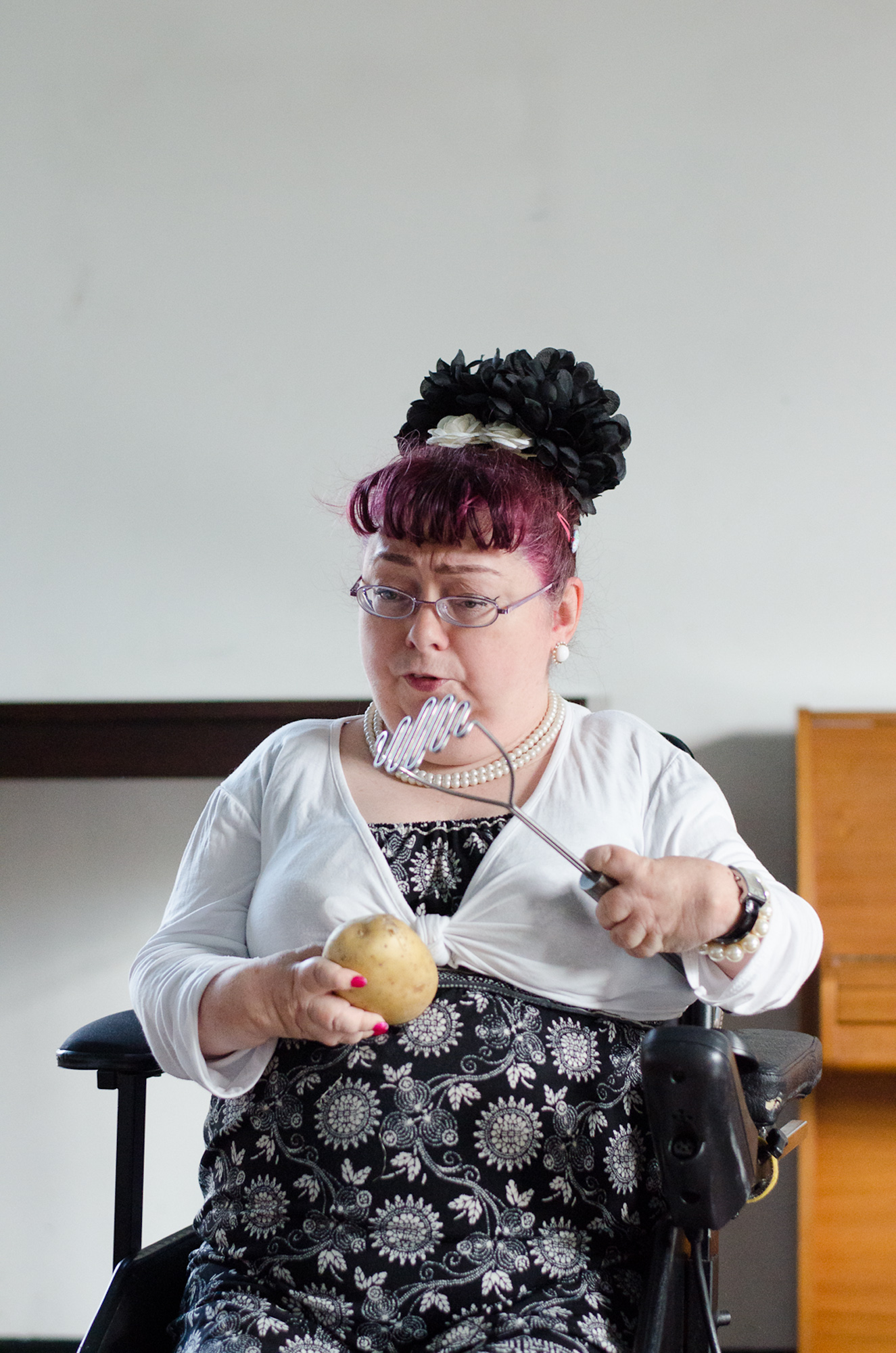 Penny holds a potato and a masher during her rehearsal of her poem Mash Up.