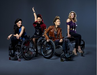 four trendy young women pose for the camera in their wheelchairs