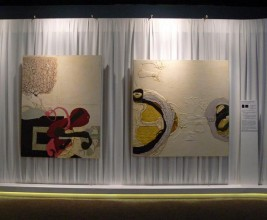 photo of two large abstract paintings against a white curtain
