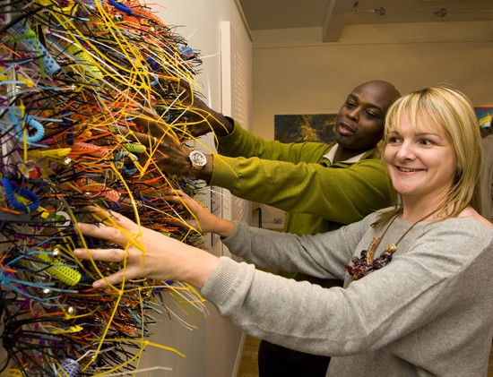 photo of a man and woman putting their hands through a three dimensional abstract artwork