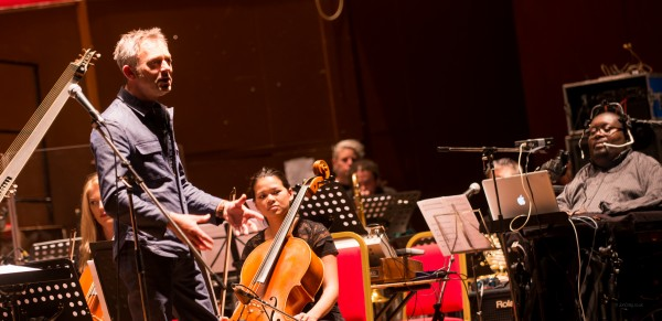 A photograph of the British Paraorchestra, inculding director Charles Hazlewood and and Clarence Adoo in rehearsals.