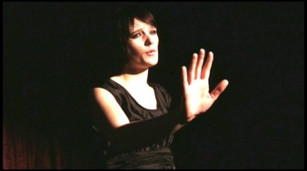 still of star of My Song, Lara Steward holding her right hand in the air.