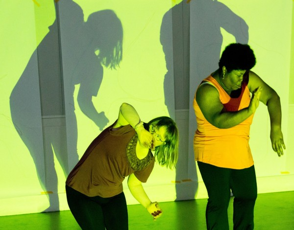 photo of two female dancers from Corali Dance company posing against a wall on which their shadows are cast in green