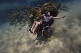woman in wheelchair underwater in tropical sea with arms stretched out and coral in the background