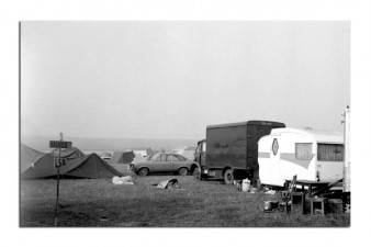 Black and white photo of vans and tents on festival site