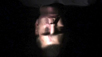 image of an upside down distorted face against a dark background taken as a still from a