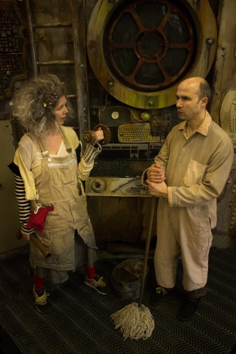 A photograph of actors Heather Gilmore as Old Woman (left) and Tim Gebbels as Old Man right in Extant's The Chairs. Tim is holding a mop and looking up, Heather is weightlifting with a small rusty object.
