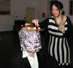 a young woman dressed in a black and white dress tentatively plucks a cheese on a stick from the head of a figure dressed completely in tin foil