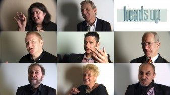 Head shots of eight people, six men, two women posed as if speaking to an interviewer sat to the left and behind the camera.
