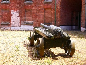 Photograph with a cannon in the foreground, and a brick built Victorian fort in the background Caroline Cardus
