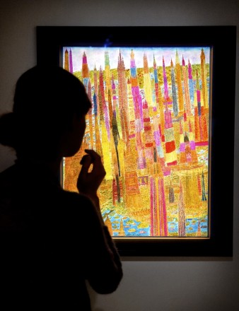 An image showing a woman looking at a brightly lit painting of a fantastical red architectural drawing in a darkened room