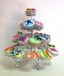 A display of 20 plaster cup cakes on a circular wire cake stand are decorated with brightly coloured pills.