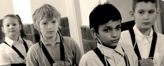 black and white still of a group of four young children wearing hearing aids