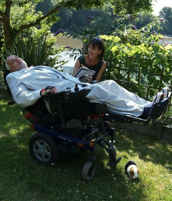 photo of Paddy Masefield trying out a reclining wheelchair, at home with his wife Caroline