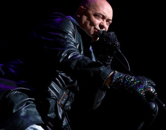 performer in black leather seen on stage is singing into a microphone