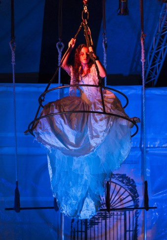 photo of a female performer in a white wedding dress, hanging from a chandelier