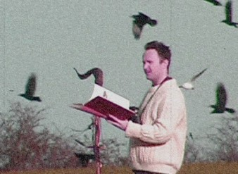 a grainy image of a man in a woolly jumper reading a book surrounded by birds