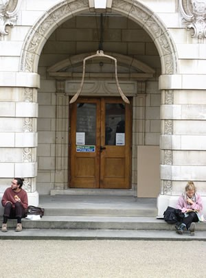 photo of two people sitting on the steps of a white-stoned public building