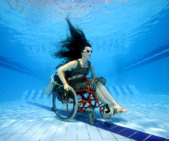 image of Sue Austin in a wheelchair photographed under water in swimming pool