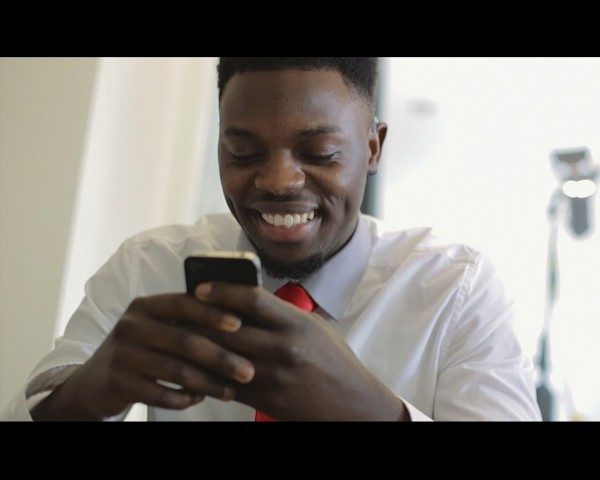 photo of a young man wearing a white shirt and tie, smiling as he looks at a text on a mobile phone