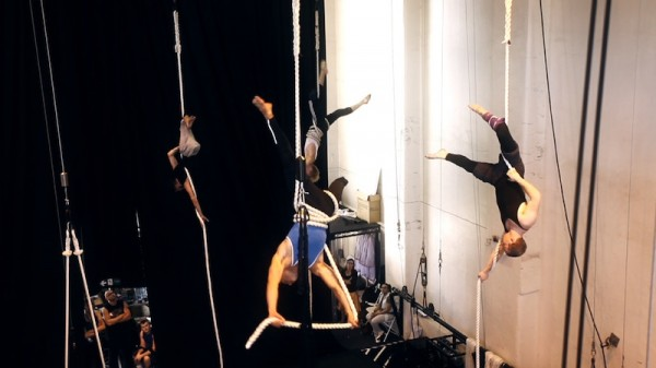 photograph of several aerialists hanging upside down from ropes suspended from a high ceiling