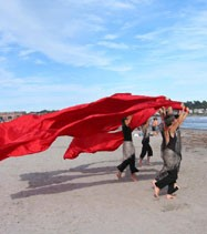 dancers with a large red cloth on a beach