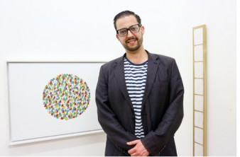 photo of deaf artist Chris Sacre in the Shape gallery standing next to one of his artworks