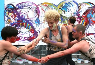 three dancers perform outdoors, covered in paint, with a large action painting in the background