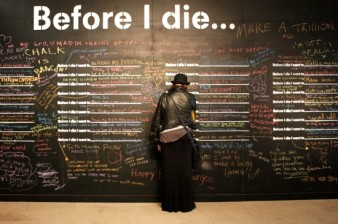 photo of a man dressed in black, writing on a wall with the caption 'Before I Die' above it
