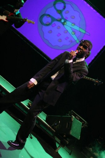 photo shows a man in a black suit with his shades on his head singing into a microphone By Jon Pratty/dao