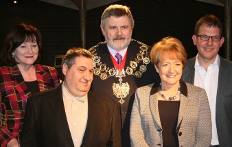 five people smile at the camera in group, all of them dressed in suits with the mayor in the centre of the group wearing his regalia