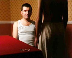 Video still of a man sitting before another man standing