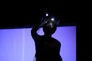 photo shows a man with a digital projector on his head looking towards us by Jon Pratty/dao