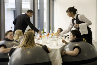 photo of diners dressed in round grey objects, being served at a dinner table