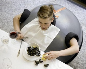 photo of young man at a dinner table, enclosed in a round object